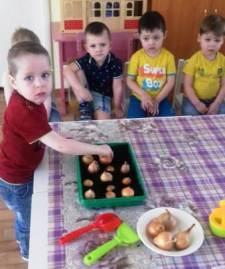 Мальчик садит лук в детском саду